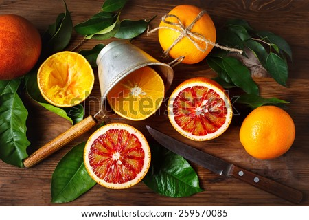 Still life with orange fruit and green leaves on wooden table. Top view.