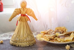 still life with pancakes and a straw doll of a traditional Slavic carnival Ukraine, Russia, Belarus - the celebration of the end of winter. pile of pancakes with butter on a table with a straw doll