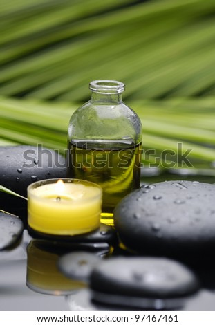 still life with pebbles and candle ,massage oil , Green leaf of palm