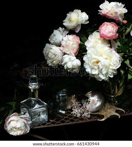 Still life with peonies .silverware and glass, black background #661430944