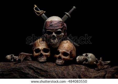 Still life with pirate skull with two swords and four head of human over creepy and darkness background