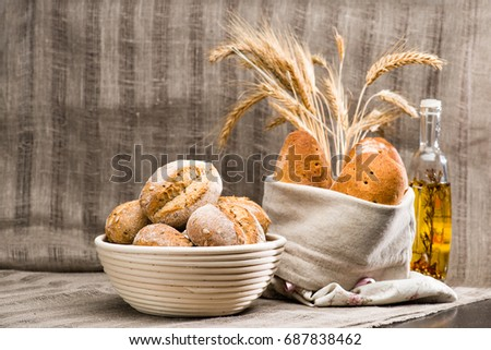 still life with pugliese Apulian bread with biga covered with white fabric, a traditional round artisan wheat bread loaves in a basket and olive oil bottle. Flat lay, textile background, shallow dof