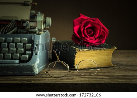 Still life with red rose bud on old book near typewriter and glasses