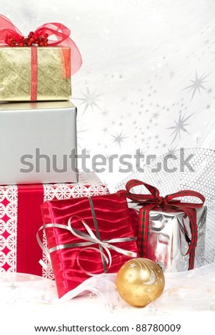 Still life with red, silver, gold wrapped Christmas gifts, pretty ribbons and ornaments. Silver star translucent fabric backdrop on white. Vertical format with copy space.