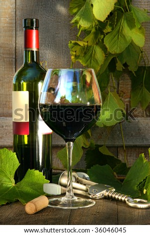 Still life with red wine bottle and glass and grapevine leaves