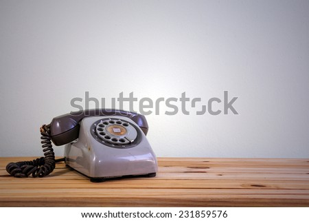 Still life with retro phone on wooden table over grunge background #231859576