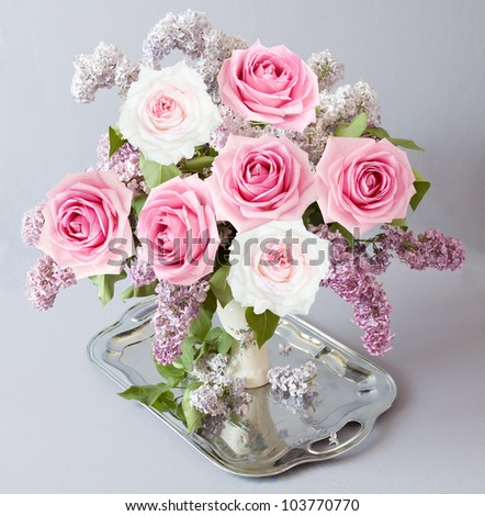 Still life with roses and lilac flowers bunch on silver tea tray on artistic background