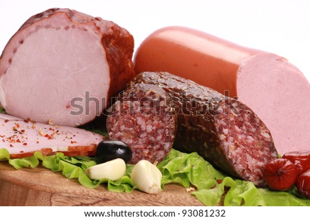 Still Life with sausages, salami and ham on a wooden table isolated on white background.