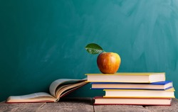 Still life with school books and apple against blackboard with