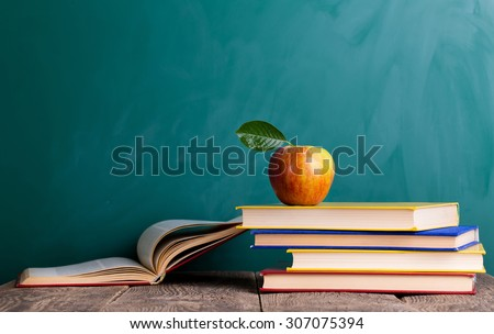 Still life with school books and apple against blackboard with \