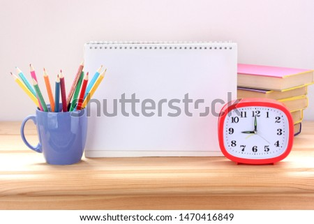 Still life with school supplies on the Desk: alarm clock, textbooks and colored pencils.  blank page in the center for Your text.