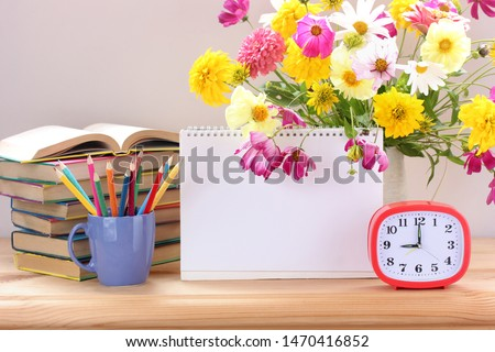 Still life with school supplies on the Desk: alarm clock, textbooks and colored pencils. September 1, knowledge day, teacher's day. Copy space.