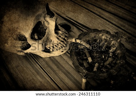 Still life with skull and cigarettes on wooden table.