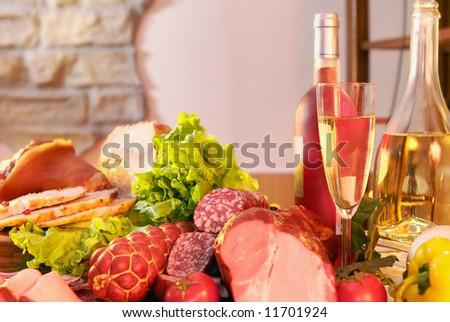 Still-life with smoked pork, sausage, green salad and wine.