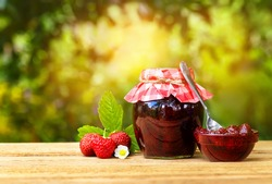 still life with strawberry jam on table with sunshine blurred natural background. Preserved fruits