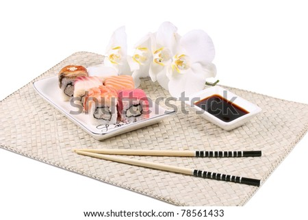 Still-life with  sushi , sticks, soya sauce and flower on bamboo mat.