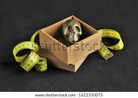 still life with tape measure ans silver scull