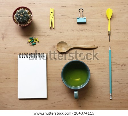 still life with tea cup and the contents of a workspace composed. Different objects on wooden table.