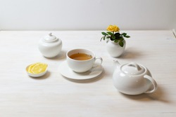 still life with tea in cup with saucer, teapot, sugar bowl, yellow rose in milk jug and lemon on white background