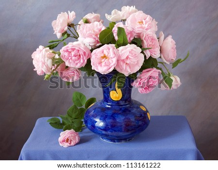 Still life with tea roses bunch in vase on artistic background