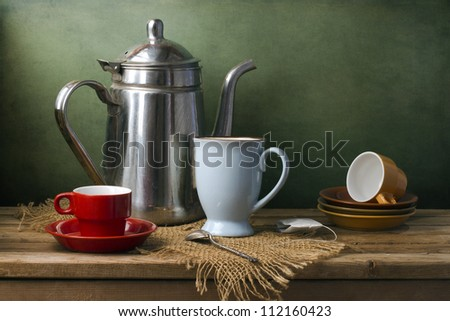 Still life with teapot and cups on wooden table