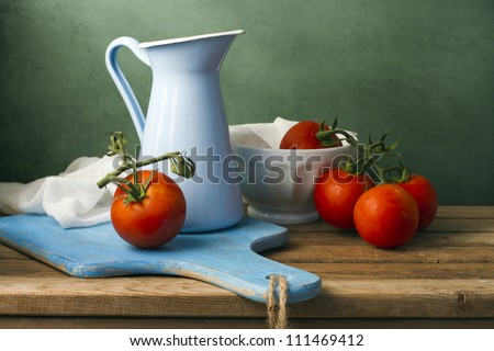Still life with tomatoes and enamel jug. Arrangement on wooden table.
