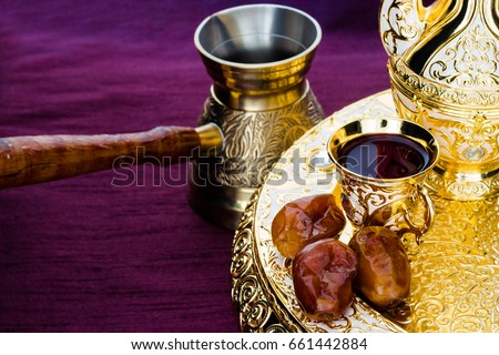 Still life with traditional golden arabic coffee set with dallah, coffee pot (jezva), cup and dates. Dark background. Horizontal photo