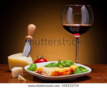 still life with traditional lasagna, red wine and cheese