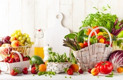 Still life with various types of fresh vegetables, fruits and berries in baskets on a white wooden table. Concept of healthy eating.