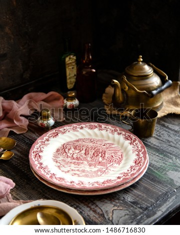 Still life with vintage plates with pink ornaments stand on rustic wooden table with brass tea pot, tea cup, spoons, saucer, old bottles, pink napkin opposite concrete wall #1486716830
