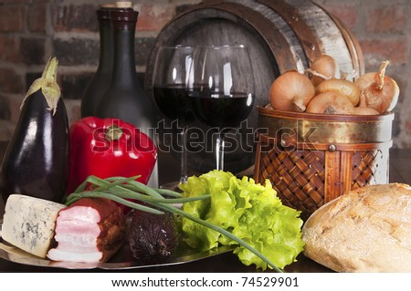 Still life with wine and vegetables, cheese and ham. Against the backdrop of a brick wall.
