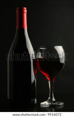 Still-life with wine bottle and footed glass over black background