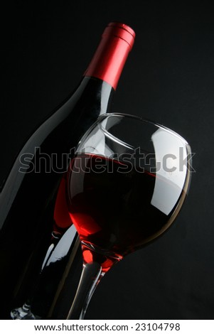 Still-life with wine bottle and glass over black background