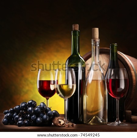 Still life with wine bottles, glasses and oak barrels.