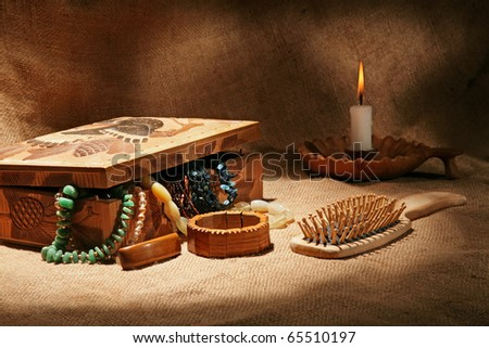 Still-life with wooden casket, ornaments, hairbrush and candle on textural background