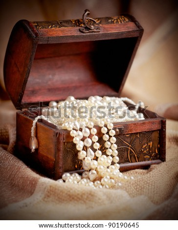 Still life with wooden treasure chest with pearl necklaces.