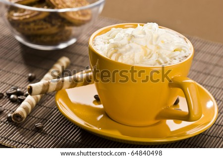 Still life with yellow cup of coffe and pastry - stock photo
