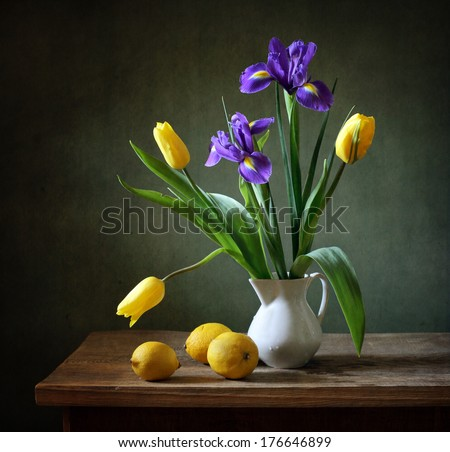 Still life with yellow tulips, irises and lemons