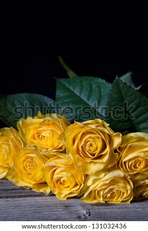 Still life with yellow withered roses on the wooden table, black background