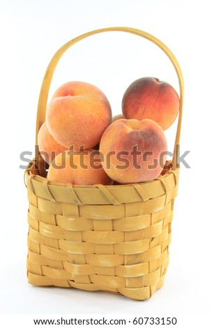 Still Picture of fresh collected from the tree Ontario peaches in wooden basket over white background.