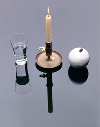 Stillife Arrangement with waterglass, holder with burning candle and white porcelain Apple on  mirror plain