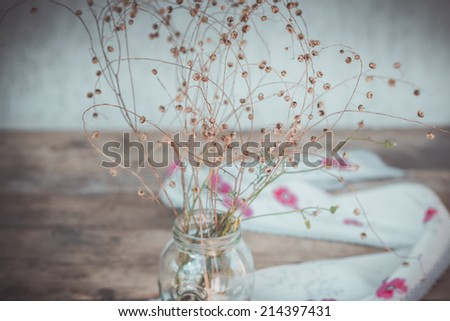 Stilllife with Dry Flowers and Scarf with Red Flowers on Wooden Background