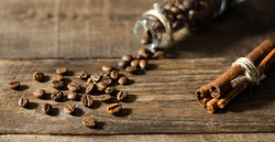 Stilllife with little bottle filled by coffee beans on the wooden background with scattered coffee beans and cinnamon