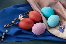 Stilllife with red, blue and pink easter eggs with willow branches and spring flower on the blue and grey cloths.