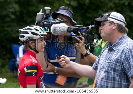 STILLWATER, MINNESOTA - JUNE 17: Reporter interviews pro cyclist Megan Guarnier following her Stillwater Criterium win at 2012 Nature Valley Grand Prix on June 17, 2012 in Stillwater.