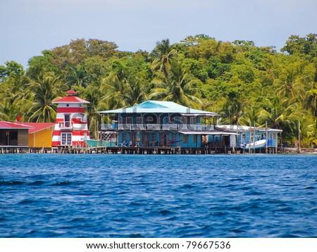 Stilt house over the sea with a lighthouse and tropical vegetation, Caribbean, Bocas del toro, Carenero island, Panama