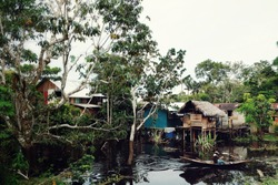 stilt houses on the amazonas river in Colombia with a man on a dugout canoe