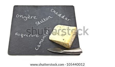 Stilton cheese on slate cheeseboard with knife with whitebackground.