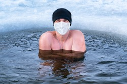 Stimulating the immune system against coronavirus by hardening the body in cold water. Smiling man in medical mask stands in cold water with ice
