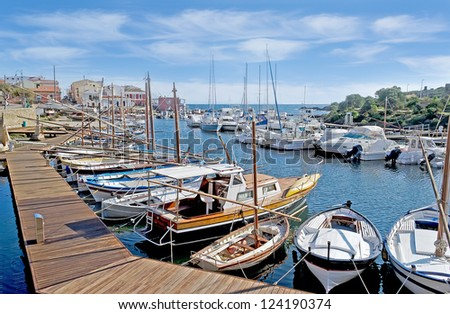 Stintino dock with boats and wooden boardwalk